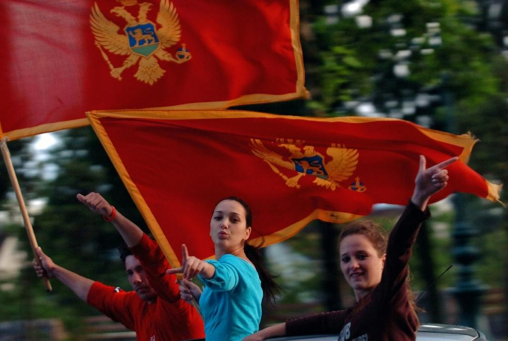 People wave Montenegro's flag in Podgorica in June 2006 following the country's formal declaration of independence from Serbia, although tensions around national identity still haunt the tiny Balkans nation to this day