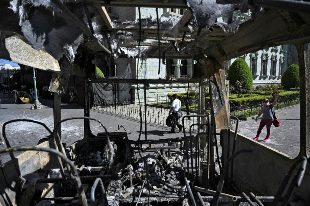 People are seen near a burnt bus a day after a protest to demand the resignation of Guatemalan President Alejandro Giammattei in Guatemala City on November 29, 2020