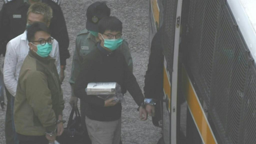 IMAGESHong Kong pro-democracy activists Joshua Wong and Ivan Lam on Wednesday exit prison to board a police van ahead of sentencing in court over a protest which took place outside the police headquarters in 2019