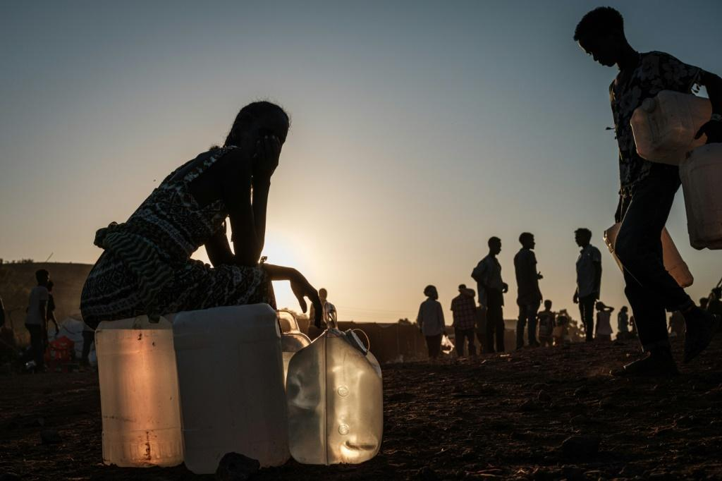 A refugee sits on a water container at the Um Raquba camp in eastern Sudan