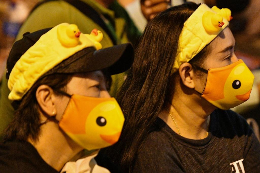 Pro-democracy protesters wear duck-themed masks and hairbands at a rally in Bangkok