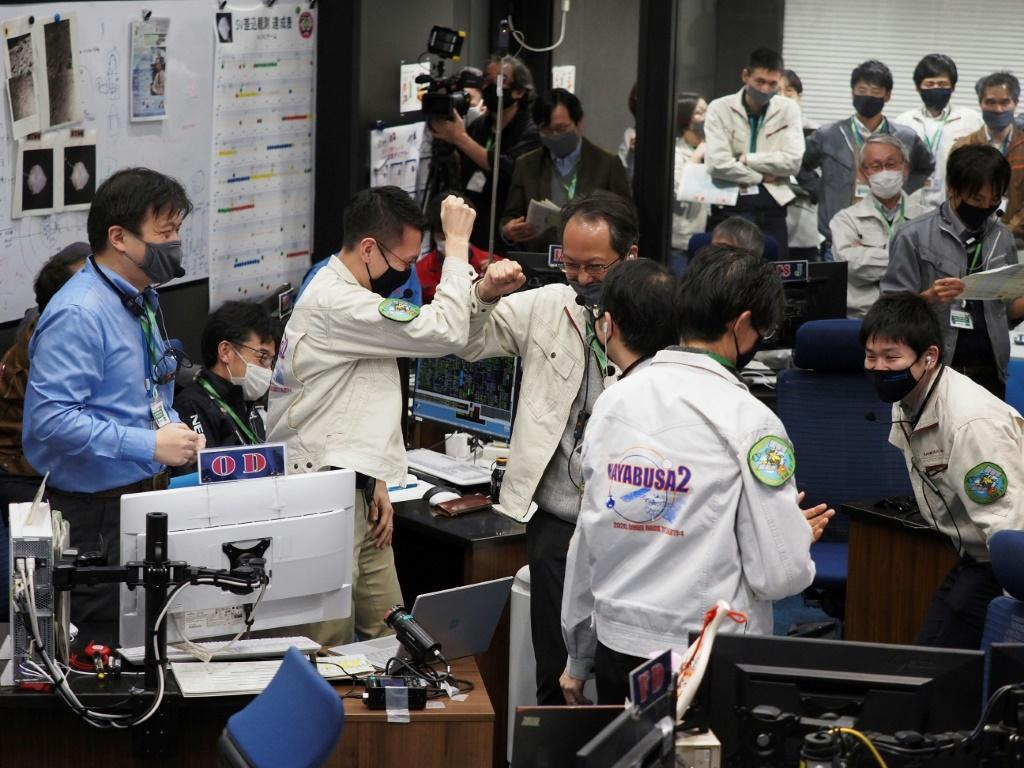 Officials from Japan's space agency JAXA celebrate after asteroid samples were dropped off on Earth by the Hayabusa-2 space probe