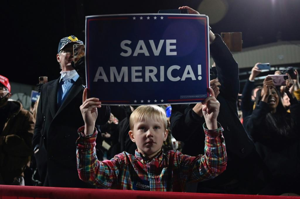 """A boy holds a """"Save America"""" sign as US President Donald Trump speaks at a tightly packed rally of thousands of mostly unmasked supporters in Valdosta, Georgia on December 5, 2020"""