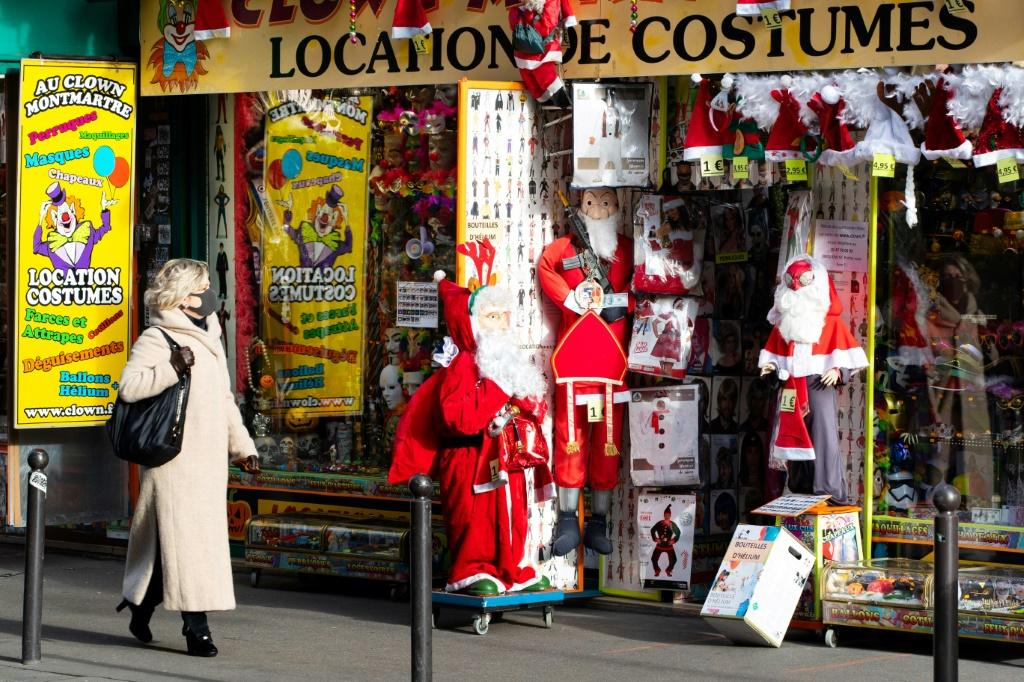 A woman walks past a costume rental store, with Santa Claus outfits outside, on December 10, 2020 in Paris as France is on a second lockdown in a bid to contain the spread of Covid-19 pandemic caused by the novel coronavirus