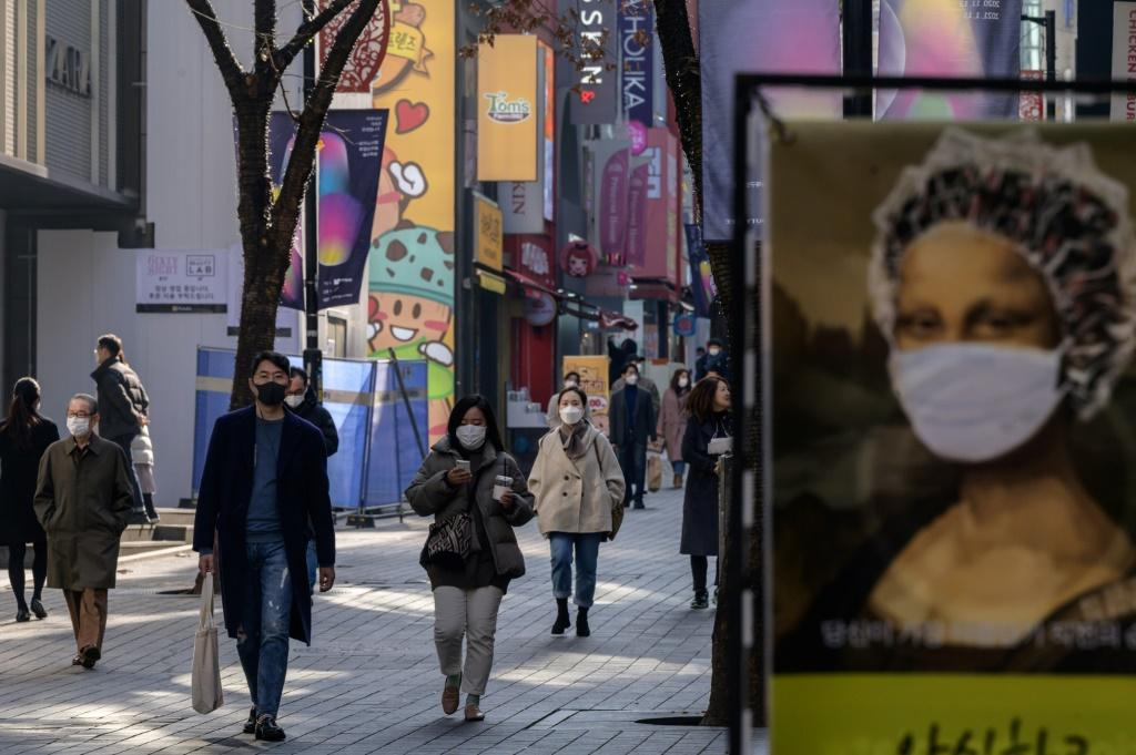 Shoppers in masks walk through Myeongdong in Seoul. Covid cases in the South Korean capital are spiking
