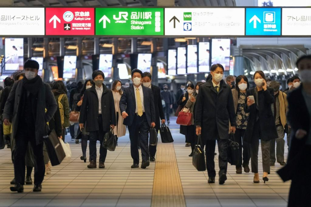 Commuters wearing face masks walk along a concourse at Shinagawa station in Tokyo