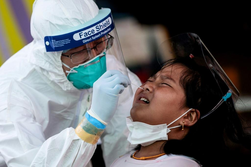Medical officials test a girl for coronavirus at the seafood market in Samut Sakhon