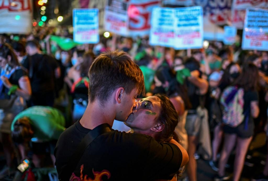 Abortion rights activists kiss outside the Argentine Congress on December 11