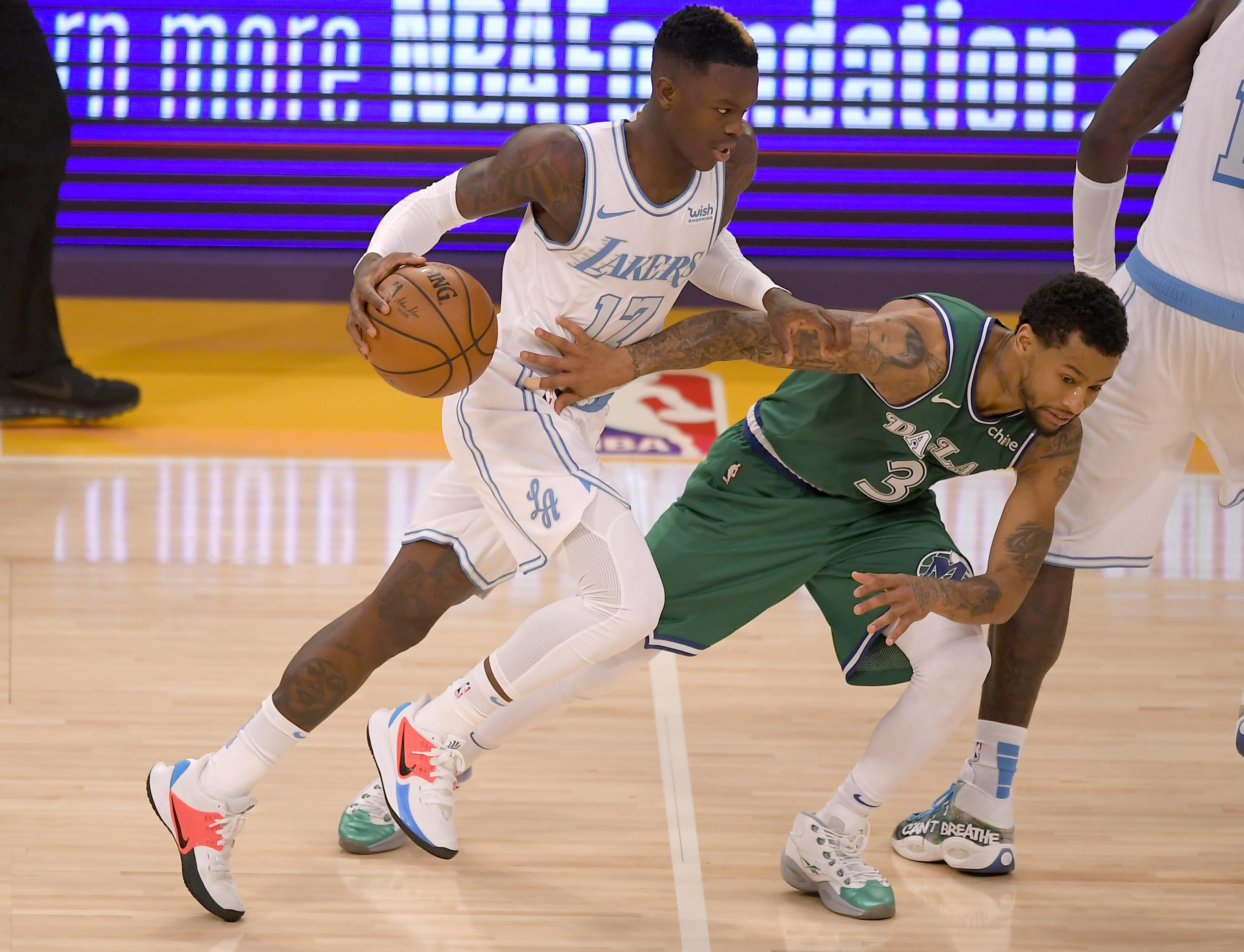 Trey Burke #3 of the Dallas Mavericks guards Dennis Schroder #17 of the Los Angeles Lakers