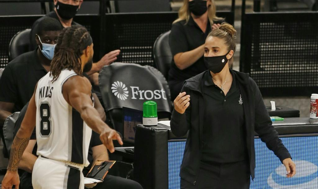San Antonio Spurs assistant coach Becky Hammon talks with Spurs player Patty Mills at AT&T Center arena in Texas