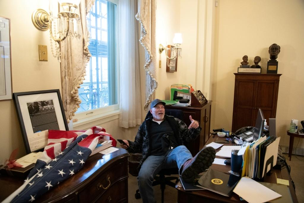 A supporter of US President Donald Trump sits inside the office of US Speaker of the House Nancy Pelosi