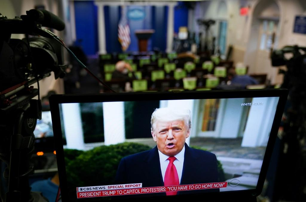 US President Donald Trump is seen on TV from a video message released on Twitter which was later taken down by the platform for breaking its rules
