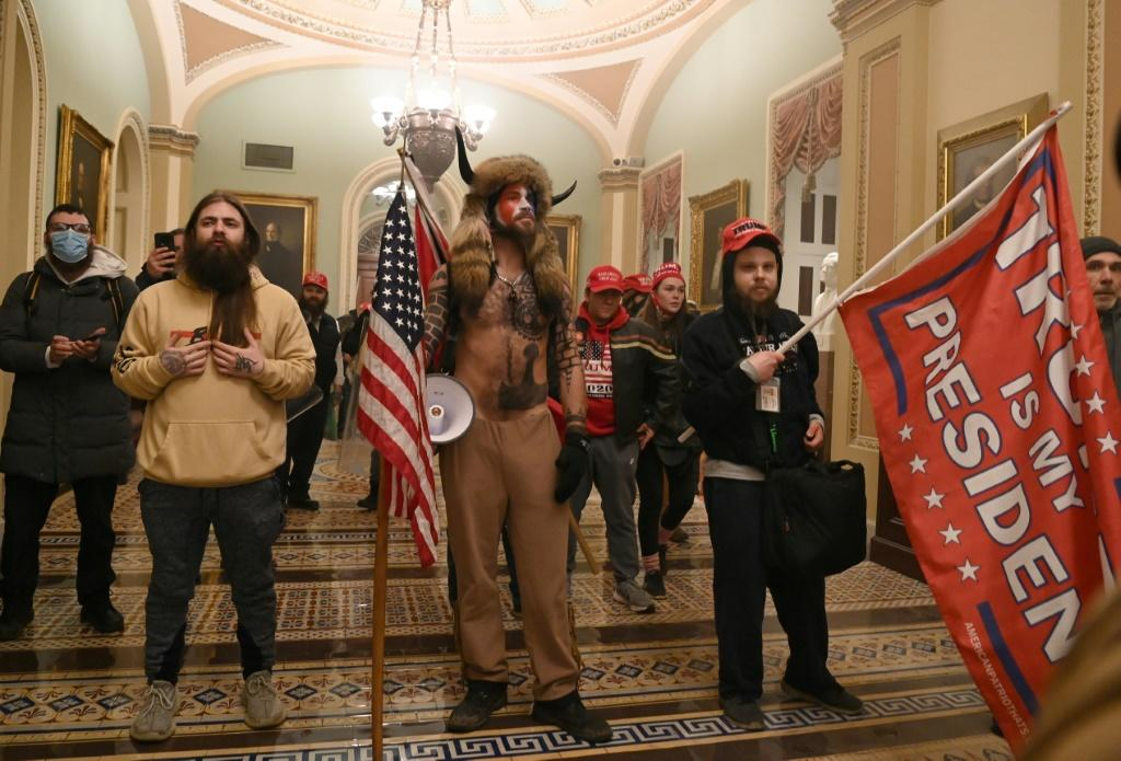 Supporters of US President Donald Trump, including member of the QAnon conspiracy group Jake Angeli, aka Yellowstone Wolf (C), enter the US Capitol