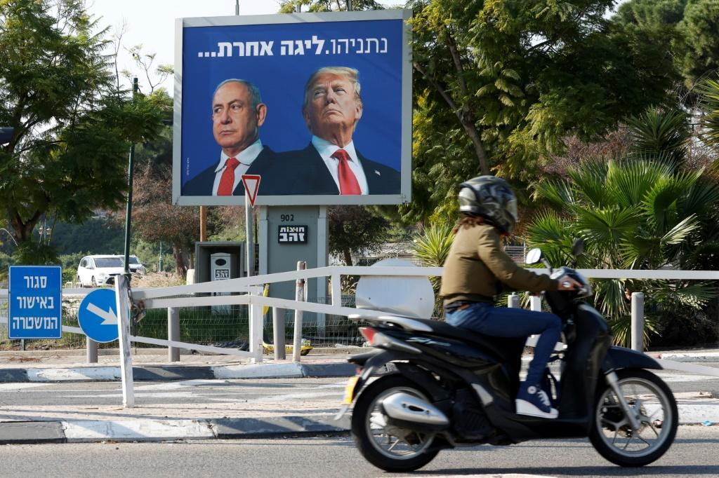 """A billboard depicting Israel's Prime Minister Benjamin Netanyahu (L) and US President Donald Trump side by side with a slogan in Hebrew which reads """"Netanyahu, a different league"""", in the Israeli coastal city of Tel Aviv"""