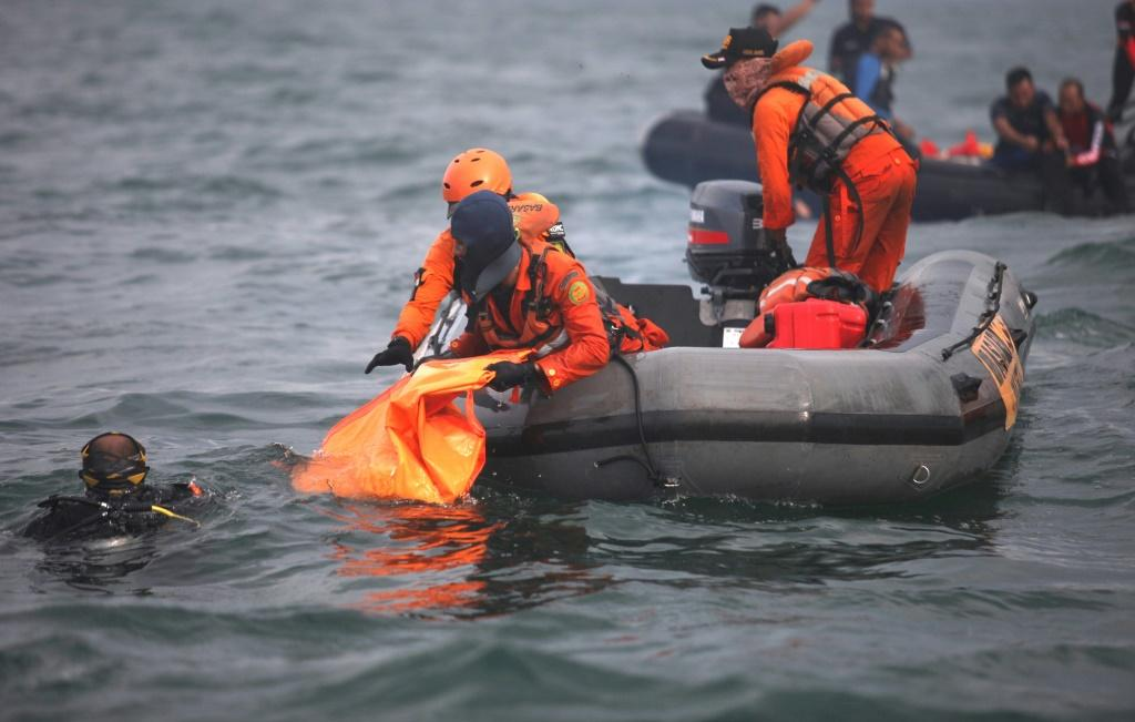 Divers are grappling with strong currents and poor weather to search for bodies and wreckage on the sea floor
