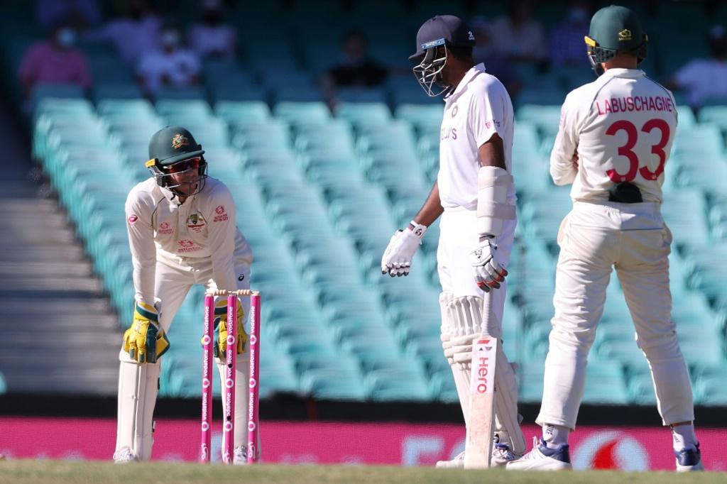 India's Ravichandran Ashwin (centre) has words with Australia captain Tim Paine (left) as Australia's Marnus Labuschagne watches during a tense final day in Sydney