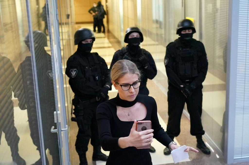 Opposition politician Lyubov Sobol uses her smartphone while standing in front of law enforcement agents in a hallway of a business centre that houses the office of opposition leader Alexei Navalny's Anti-Corruption Foundation (FBK), in Moscow in December