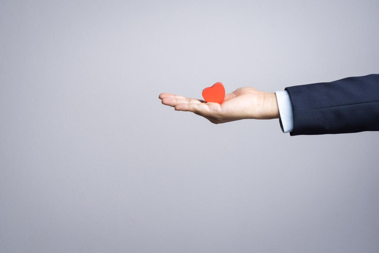 Business man hand with wooden red heart object
