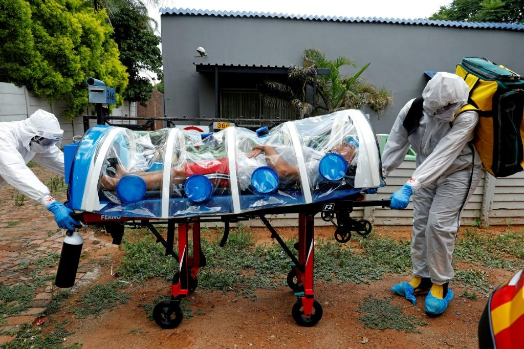 Paramedics take a man showing symptoms of COVID-19 to hospital near Pretoria in South Africa. A new strain of the virus that emerged in the country is already spreading around the world