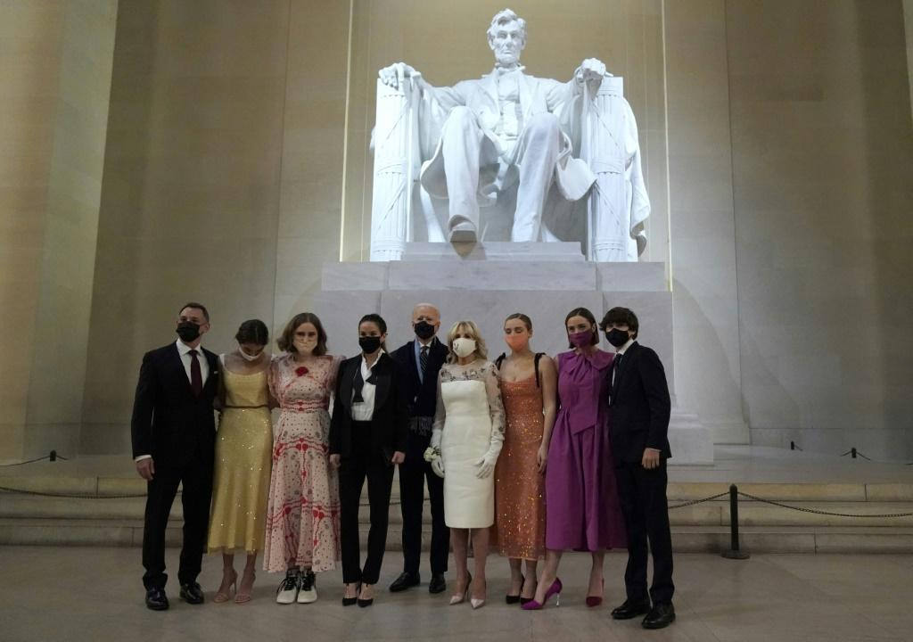 """The new """"first family"""" of the United States pose in front of a statue of Abraham Lincoln while wearing face masks following Joe Biden's inauguration"""