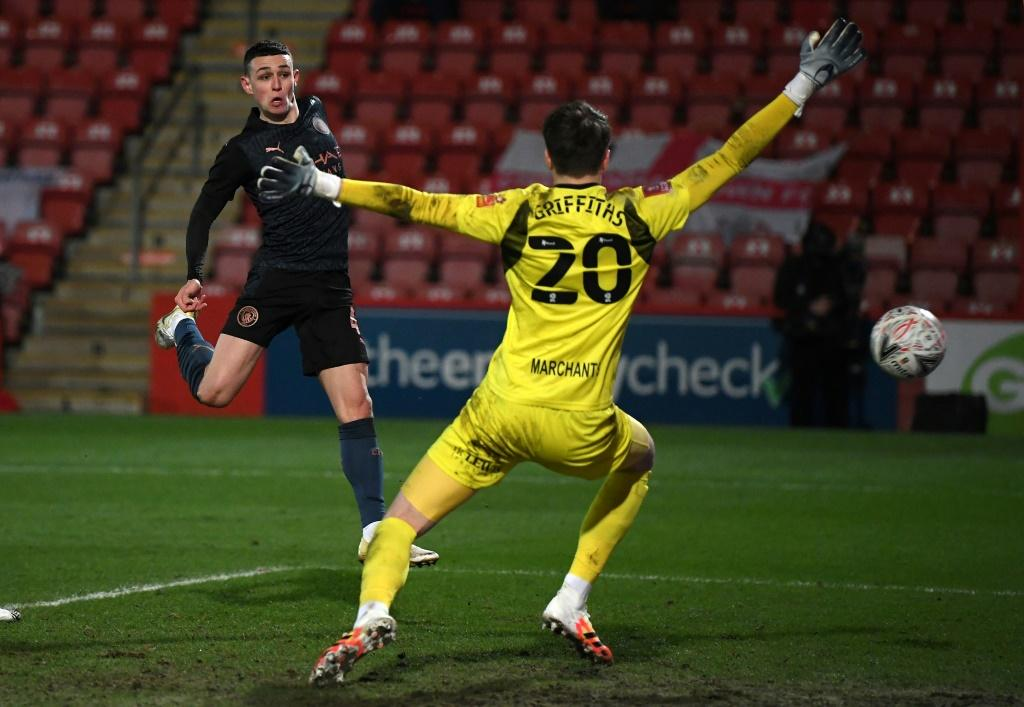 Manchester City midfielder Phil Foden (left) scores against Cheltenham in the FA Cup fourth round