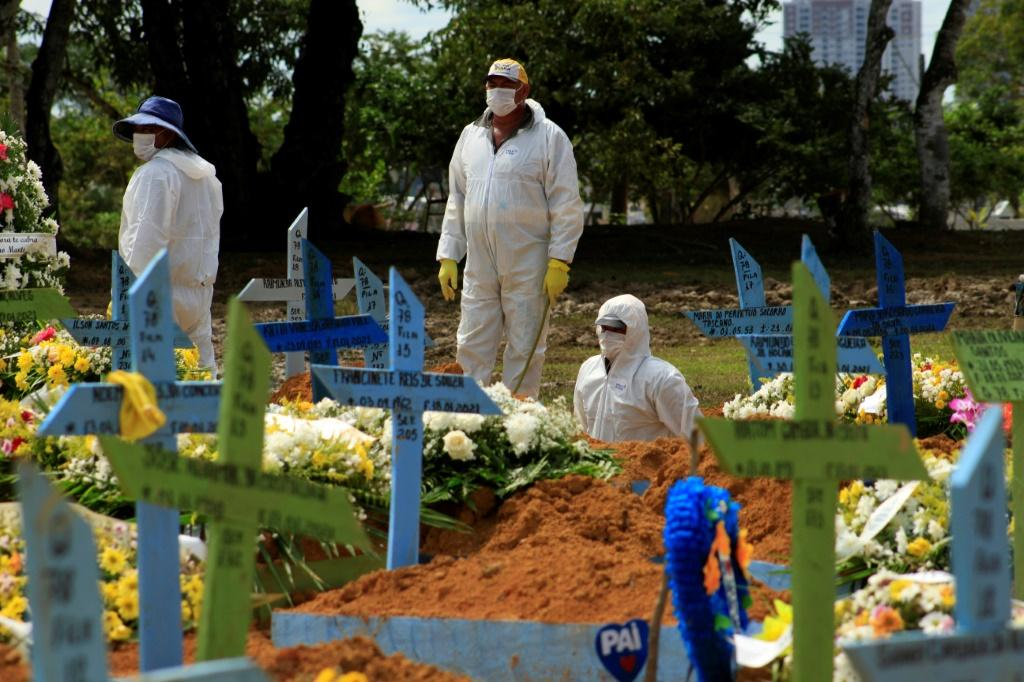 Gravediggers pictured during a funeral of a COVID-19 victim at the Nossa Senhora Aparecida cemetery in Manaus, Amazonas state, Brazil