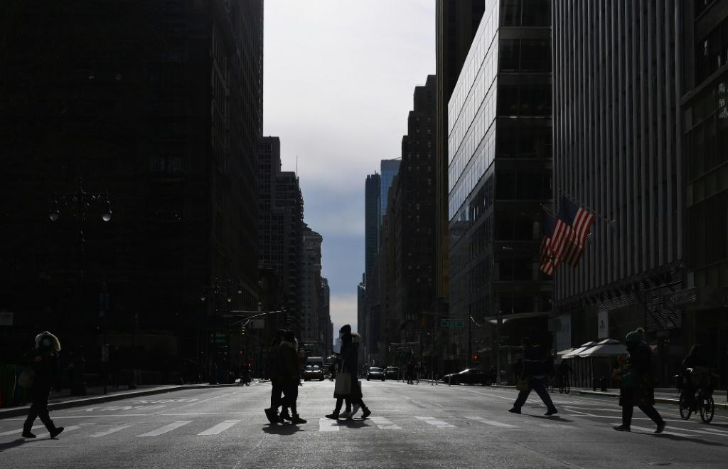 People walk through the usually bustling midtown area of Manhattan during lunchtime on January 25, 2021 in New York City