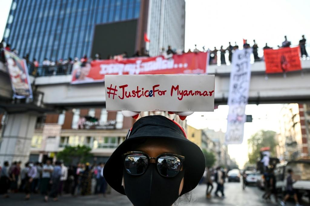 A protester wears a sign with a hashtag #justiceformyanmar as they take part in a demonstration against the military coup in Yangon on February 8