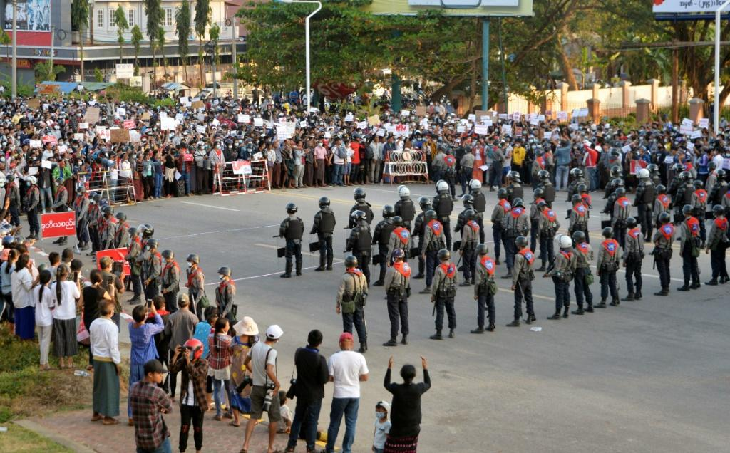 Protesters face off with police standing guard on a road during a demostration against the military coup in Naypyidaw on February 8