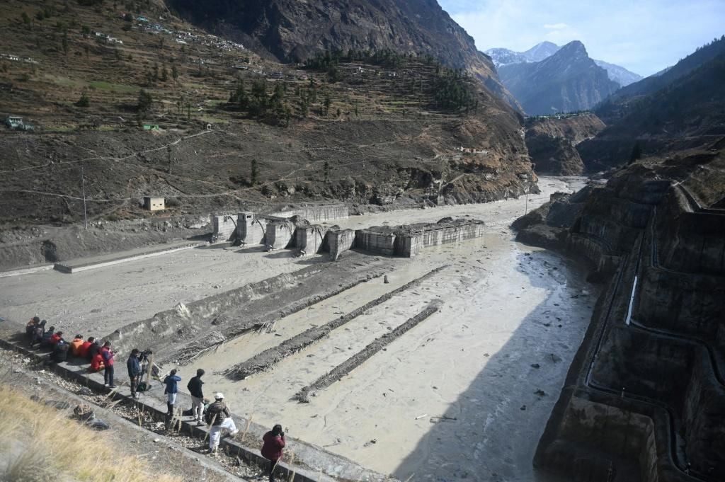 People look at the remains of a dam along a river in Tapovan of Chamoli district, destroyed after a flash flood thought to have been caused when a glacier burst