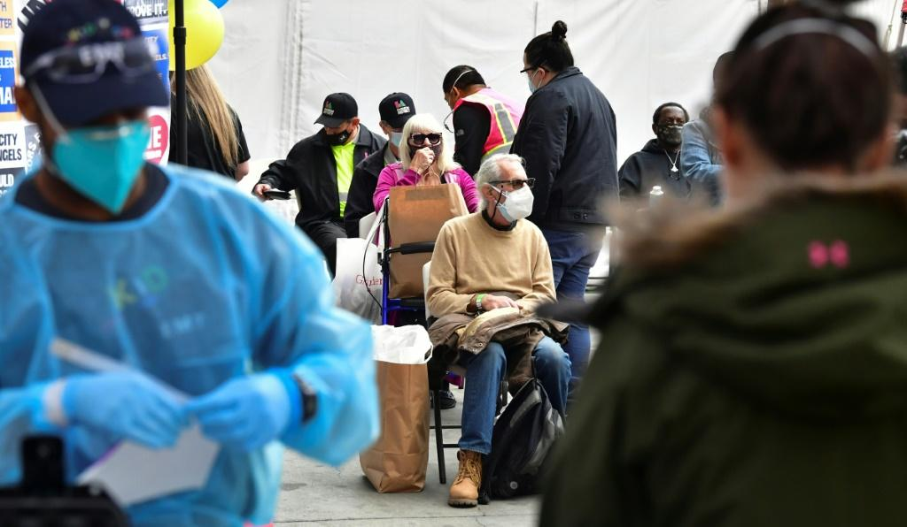Vaccinated seniors are seated in a waiting area before departure during a distribution of Covid-19 vaccines to seniors above the age of 65 who are experiencing homelessness in Los Angeles