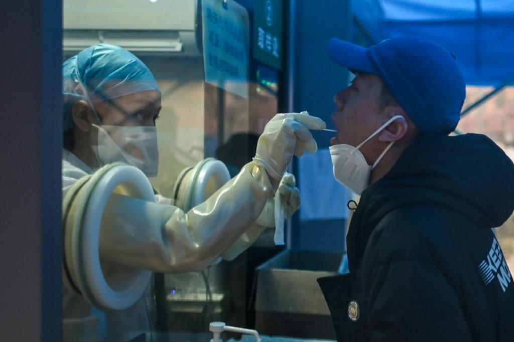 A health worker takes a swab sample from a resident in the Chinese city of Wuhan, which WHO experts visited in a attempt to discover the orgins of the Covid-19 virus