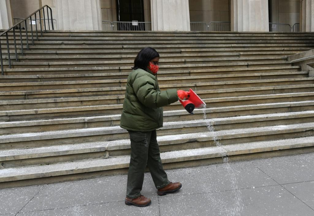 A worker distributes salt in preparation for a snow storm at Wall Street in New York