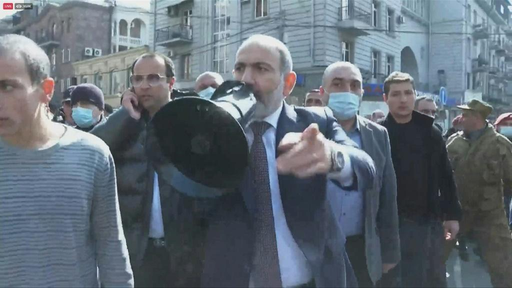 Armenian Prime Minister Nikol Pashinyan marches through the streets of the capital Yerevan with his supporters after accusing the military of mounting an attempted coup.