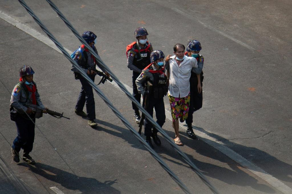 Police escort an arrested man, amid a crackdown on protests against the military coup, in Yangon on February 26, 2021