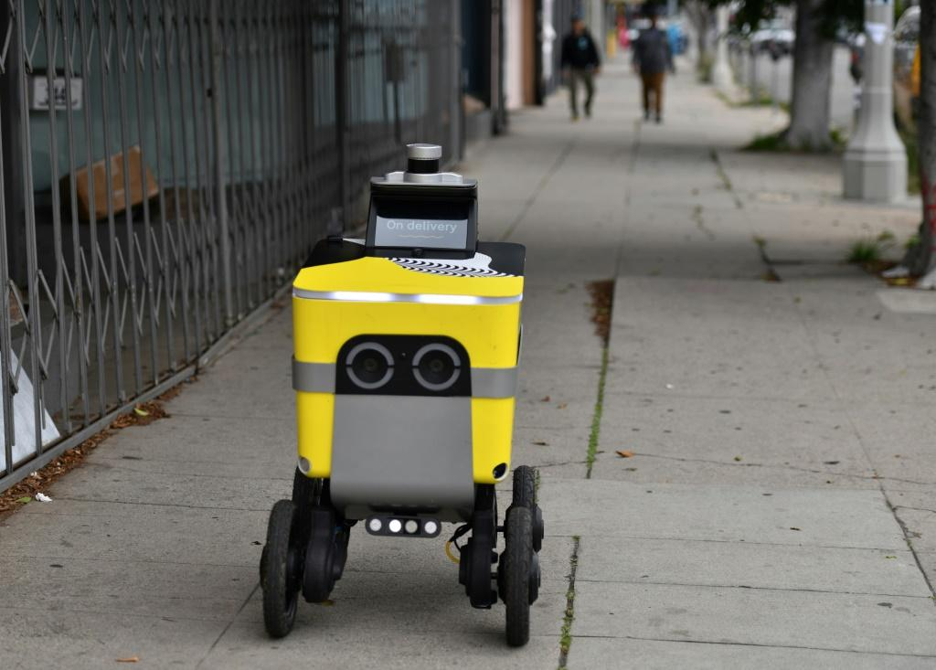 A Postmates robot brings food to customers in Los Angeles -- the robotics division of Postmates, acquired by Uber last year, will be spun out as an independent company