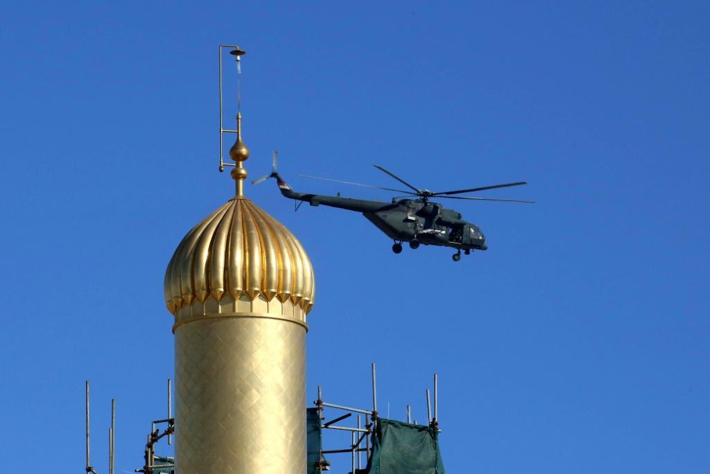 An Iraqi military helicopter flies over the Imam Ali mausoleum in Najaf as authorities lay on tight security in the shrine city for a landmark meeting between Pope Francis and top Shiite cleric Grand Ayatollah Ali Sistani