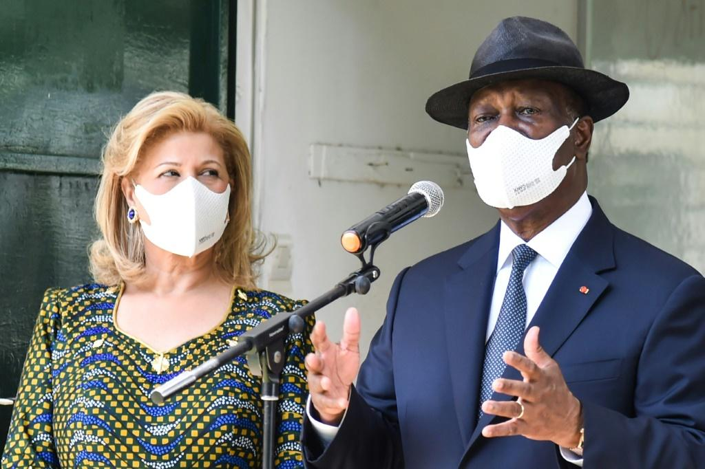 President Ouattara, with his wife Dominique, speaks to reporters after casting his vote