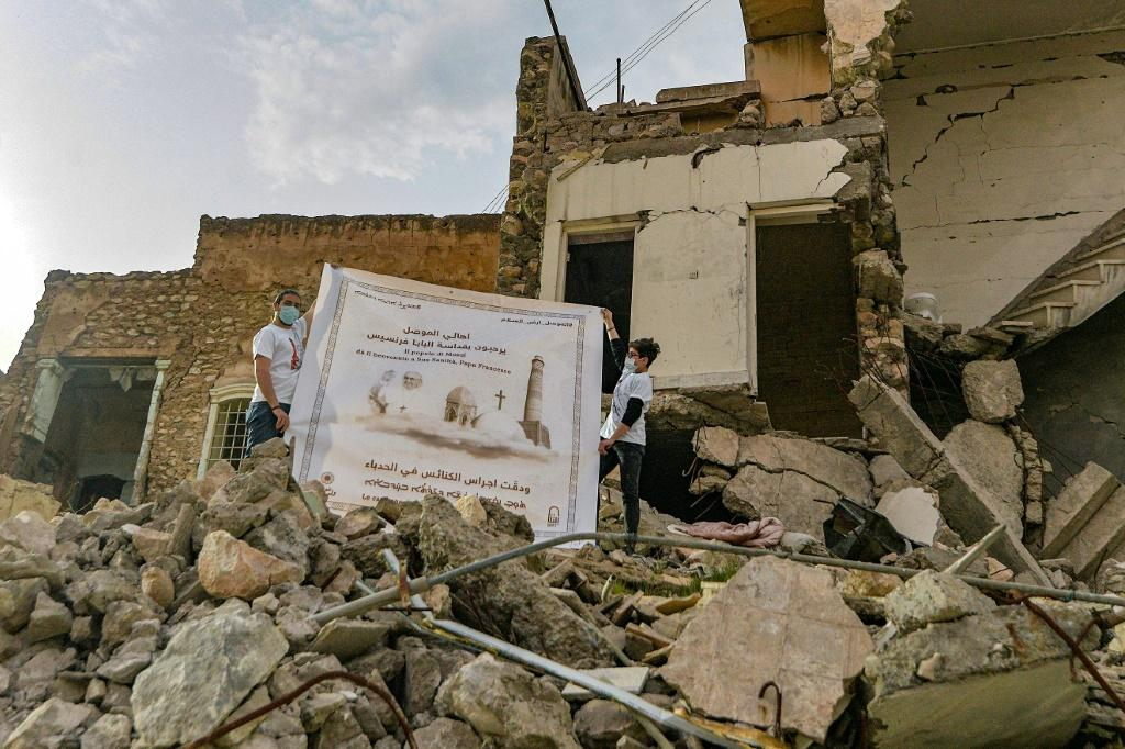 Youth unfolded a poster who welcomed Francis to the ruins of the Syrian Catholic Church for the Immaculate Conception in Mosul