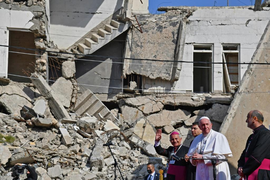 Pope Francis, accompanied by the Chaldean Catholic Archbishop of Mosul Najib Michaeel Moussa, near the ruins of the Syriac Catholic Church of the Immaculate Conception in the old city of Iraq's Mosul