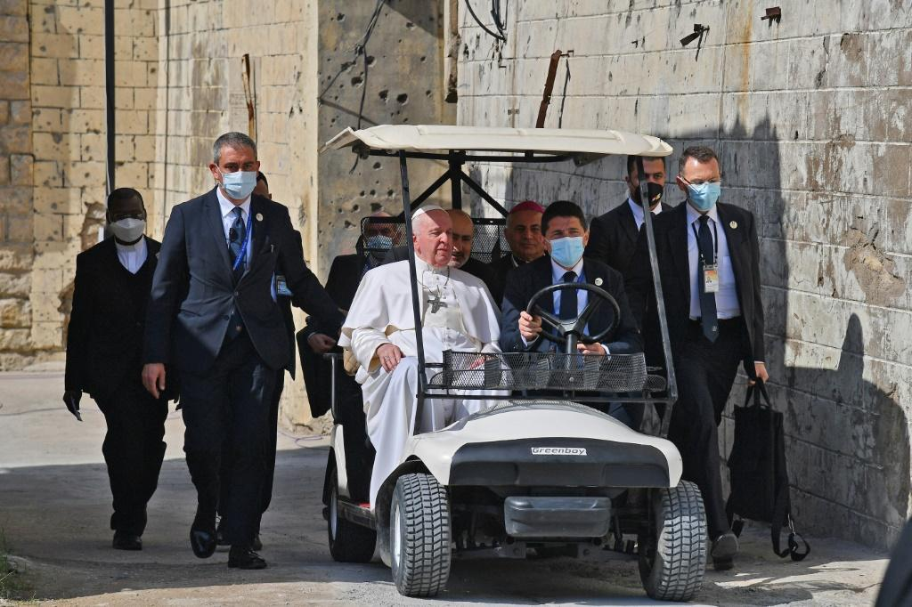 Pope Francis rides in a golf cart in the old city of Iraq's northern Mosul