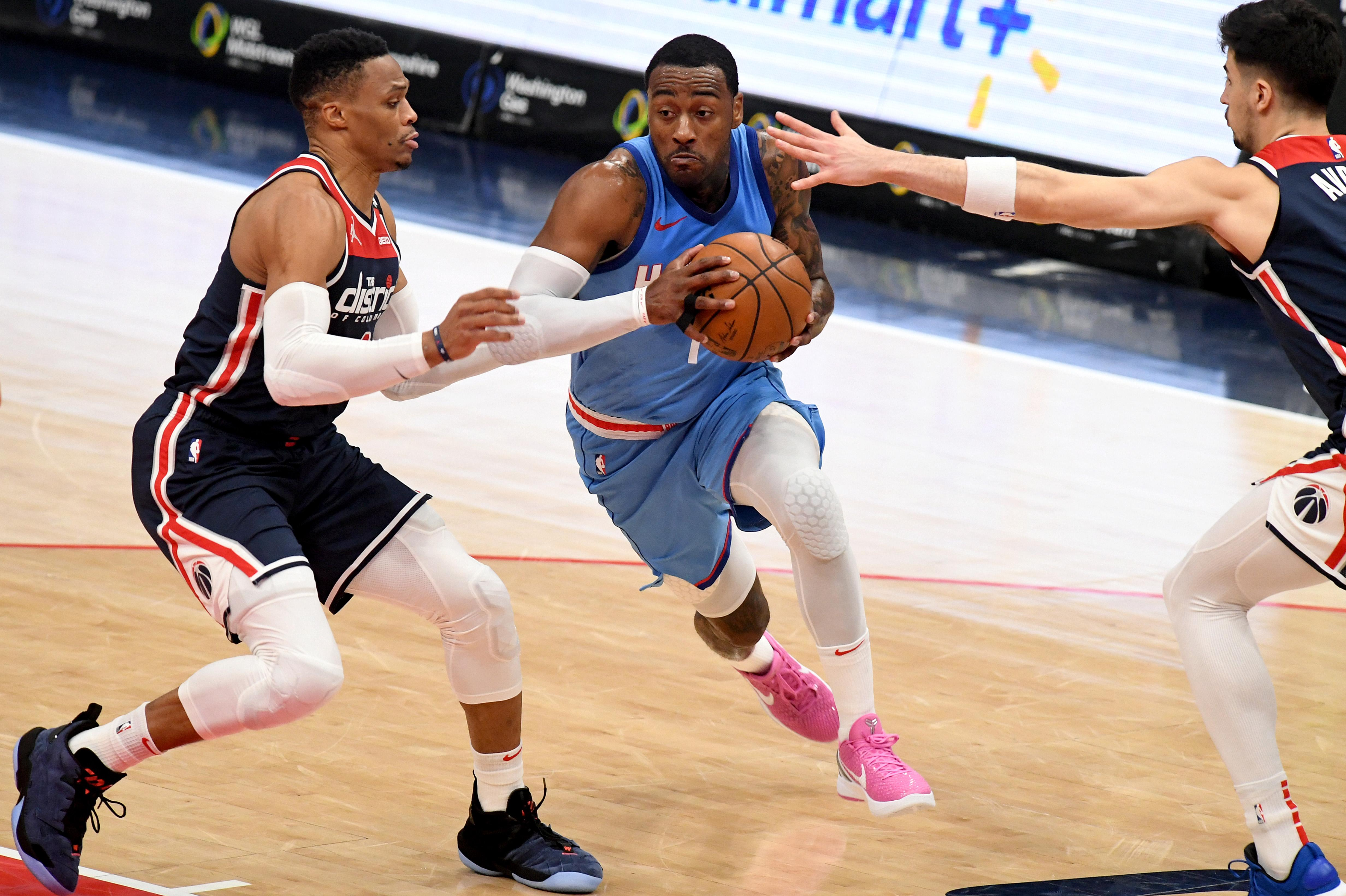 John Wall #1 of the Houston Rockets dribbles in front of Russell Westbrook #4 of the Washington Wizards