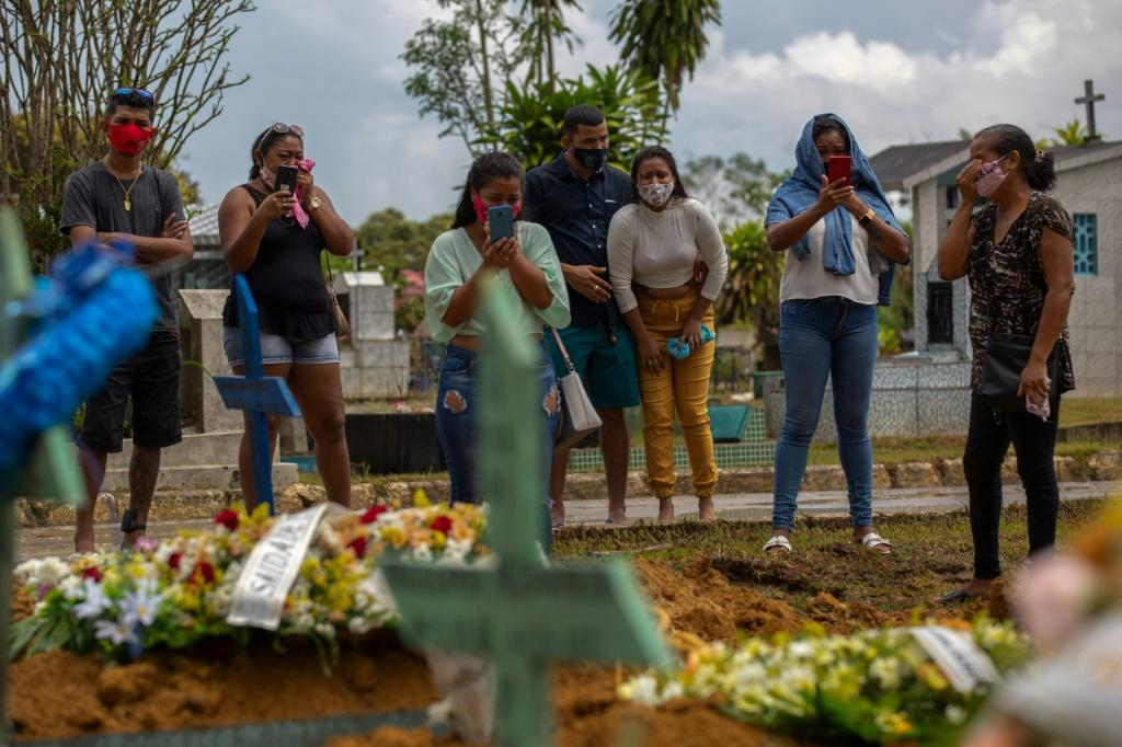 Relatives of a Covid-19 victim attend a funeral in Brazil, where the daily death toll is soaring
