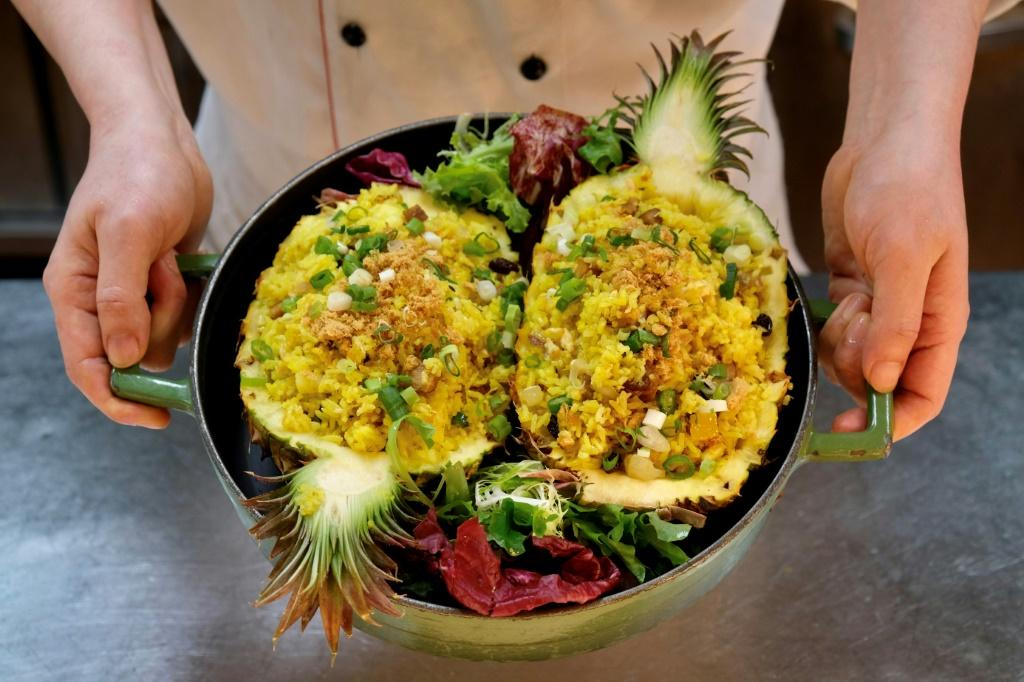 A restaurant employee holding a dish of pineapple fried rice at the Courtyard by Marriott hotel in Taipei