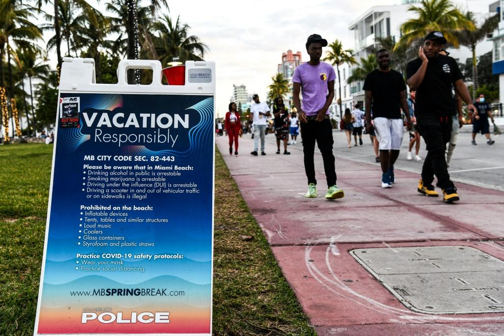 A sign asking vacationners to follow Covid-19 safety protocols in Miami Beach
