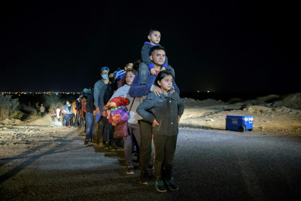 A family of immigrants stand in line with others at a processing checkpoint before being detained at a holding facility by US Border Patrol agents in the Texas border city of Roma
