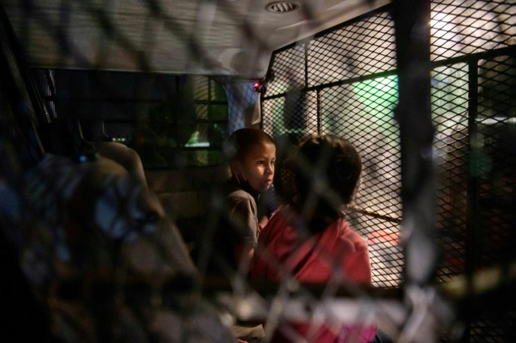 Two unaccompanied seven-year-old children wait in a Border Patrol van for processing after crossing the Rio Grande into Texas