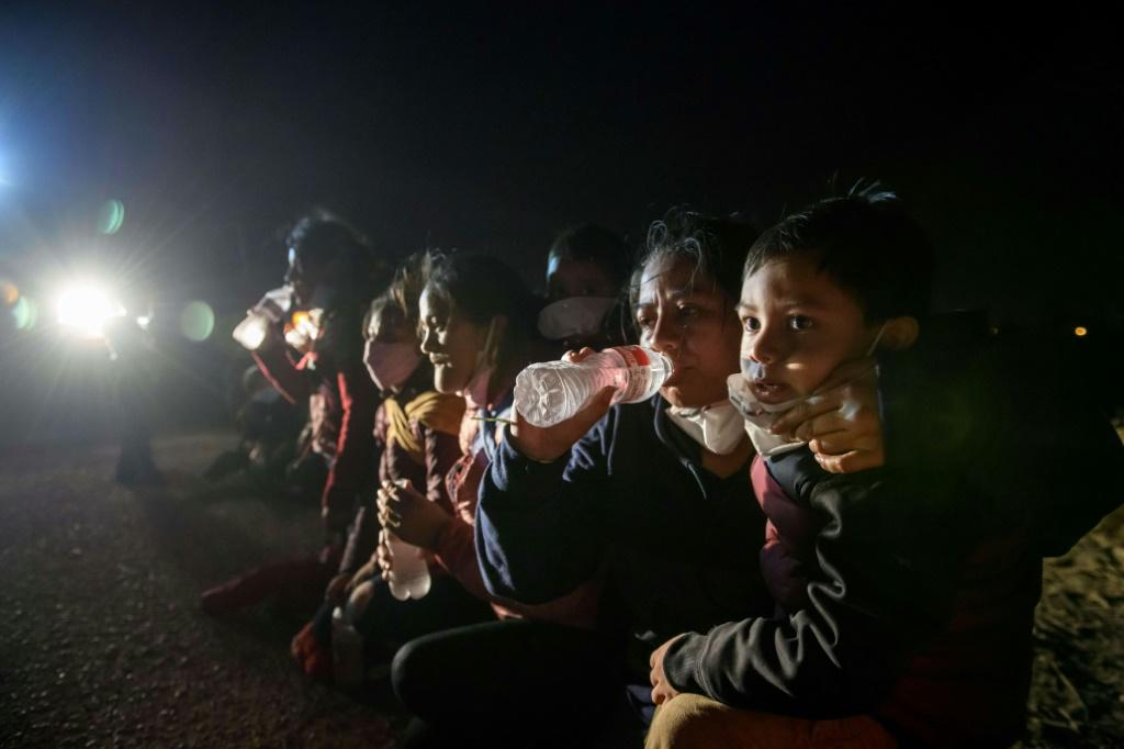 Women and children drink water and wait to be processed by US Border Patrol agents after crossing the Rio Grande from Mexico to Texas