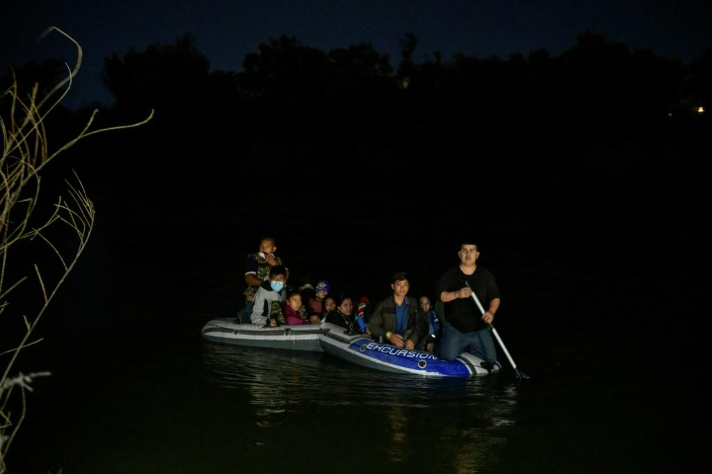 A Mexican people trafficker rows a small boat across the Rio Grande carrying Guatemalan and Honduran migrants from Miguel Aleman, Mexico, to Roma, Texas, March 28, 2021
