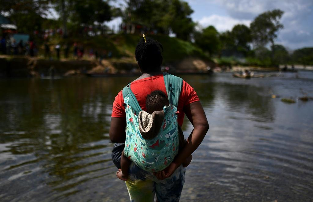 A migrant carrying a baby crosses the Chucunaque river after walking for five days in the Darien Gap